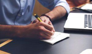 紙に文字を書く男性の写真